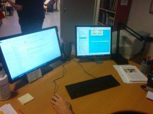 Nuotraukoje matomi du kompiuteriai, kurių ekranuose yra parodytas viso teksto knygos pavyzdys. Tekstas eina kartu su garsu ir pabraukia skaitomą žodį.